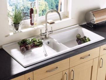 Современные кухонные гарнитуры, как правило, укомплектованы мойкой. Она является важной составной частью данной мебели, и ее дизайну и особенностям, как и свойствам смесителя, уделяется достаточно внимания. Немаловажно и то, из какого материала она изготовлена. Сегодня мойку можно приобрести отдельно от гарнитура, вмести с ним, а также заказать ее изготовление по индивидуальному эскизу.  Основными требованиями, предъявляемыми к мойке, считаются ее привлекательность и функциональность. Форма мойки выбирается исходя из имеющегося дизайна, как самого помещения, так и кухонного гарнитура. Она может быть круглой, прямоугольной, островной, угловой. Кроме того, мойка может состоять из одной, полутора или двух чаш. Существуют также мойки с крылом или без него.   Согласно статистике, большинство покупателей останавливают свой выбор на квадратных или прямоугольных чашах. Данная форма идеально подходит для стандартной кухни, которая вряд ли поразит ваше воображение особенностью дизайна. Установлено, что мойки такой формы занимают меньше всего площади. Круглая мойка посуды вместит меньше, а вот площади займет больше.    Виды кухонных моек Довольно удобным вариантом считается мойка, состоящая из двух чаш. В одной из них можно мыть посуду, а вторую использовать для других целей, например для размораживания мяса. Однако ее трудно поместить на кухне небольших размеров. Если у вас возникла такая проблема, то можно приобрести полуторчашевую мойку с одной большой и одной маленькой чашей.  Многие хозяйки успешно справляются и с одночашевой мойкой, в особенности, если у нее есть крыло, которые можно использовать как сушилку. На крыло, обычно выкладывают горячую или только что вымытую посуду. Сюда же можно выложить и продукты. При этом вода с крыла стекает в чашу или сливное отверстие, которое выводится к канализации. Бывают мойки с двумя крыльями.  Выбор глубины чаши зависит от того, как часто и много вы готовите. Если глубина мойки слишком большая, а ваш рост выше среднего, то во время